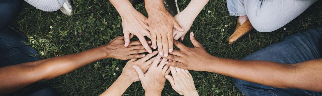 group of people with there hands in the middle