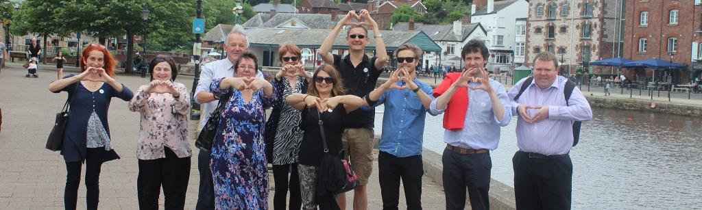 LOVE Devon making a heart symbol with their hands next to a river